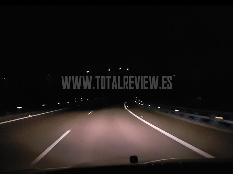 luces de cruce de coche en carretera